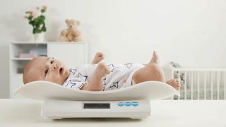 cute baby being weighed on a scale at home