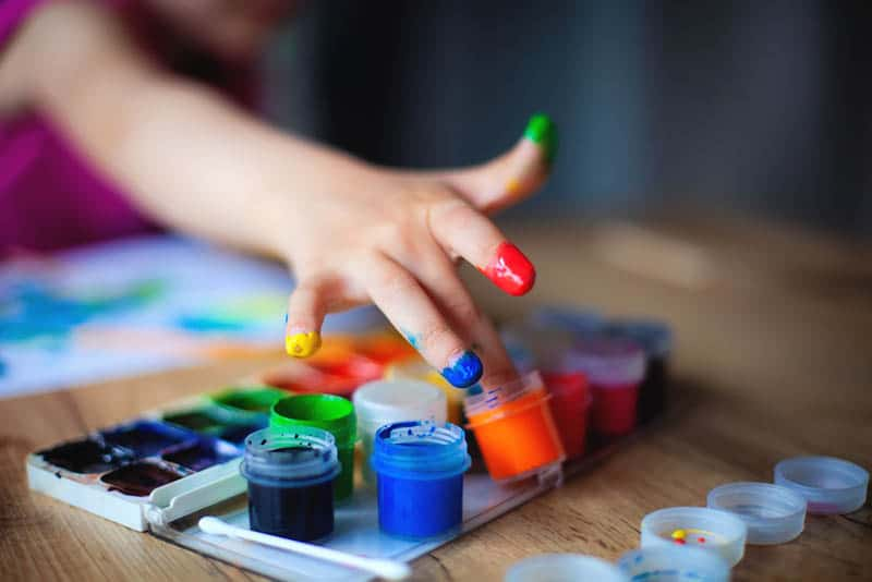 kid coloring fingers in differents colors on the wodden table