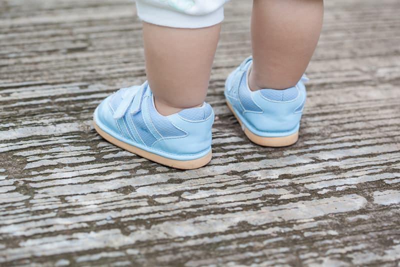 little baby walking in blue shoes on wooden floor