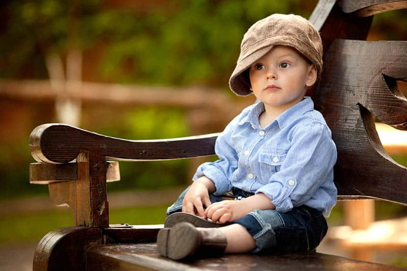 little boy wearing big hat sitting on the bench in the park