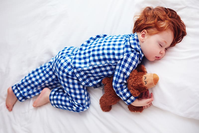 little boy wearing cotton pijama sleeping with toy