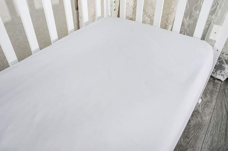 mattress with white sheet on in the toddler bed in the bedroom