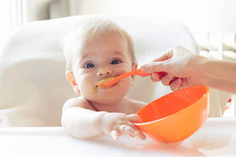 mother feeding baby with food from orange bowl and orange spoon
