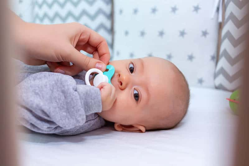 mother taking a pacifier from her baby in the crib