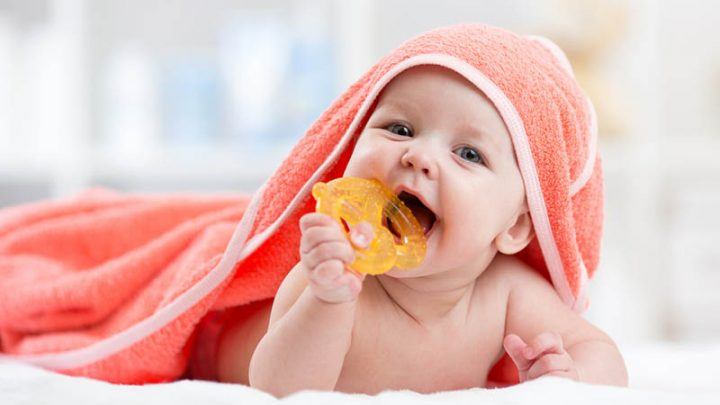 cute baby covered with orange towel chewing teether on bed