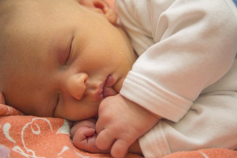 newborn baby with jaundice sleeping on bed