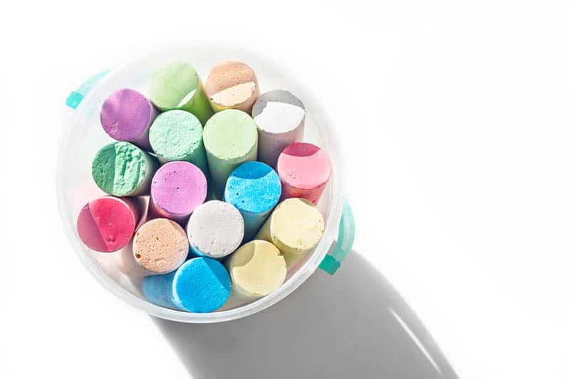 pack of sidewalk chalks in a plastic bucket on the white table with shadow