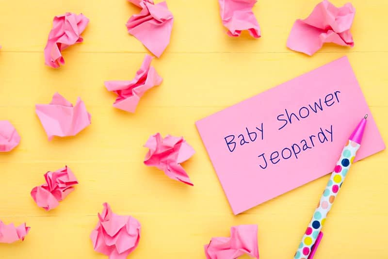 pink paper with written name of the baby shower games with pen on the yellow table