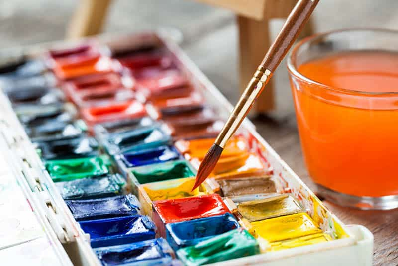 set of watercolor paints with tiny brush and a glass of colored water