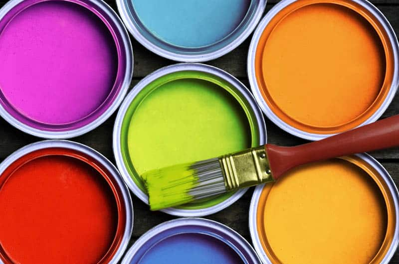 seven colorful paints with brush on the wooden table