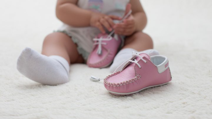 baby girl sitting on floor and playing with pink shoes
