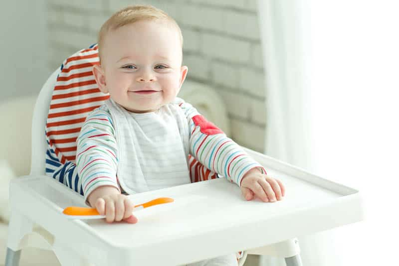 smiling baby sitting in high chair and waiting for food