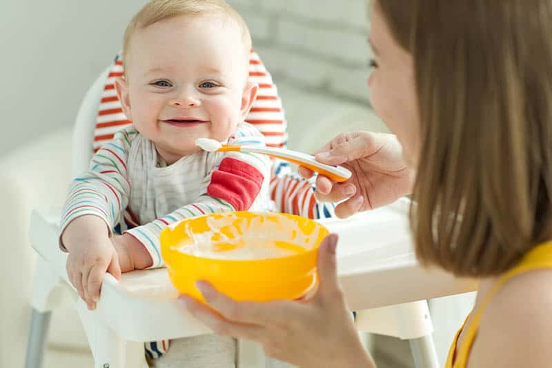 smiling mother trying to feed smiling baby in high chair