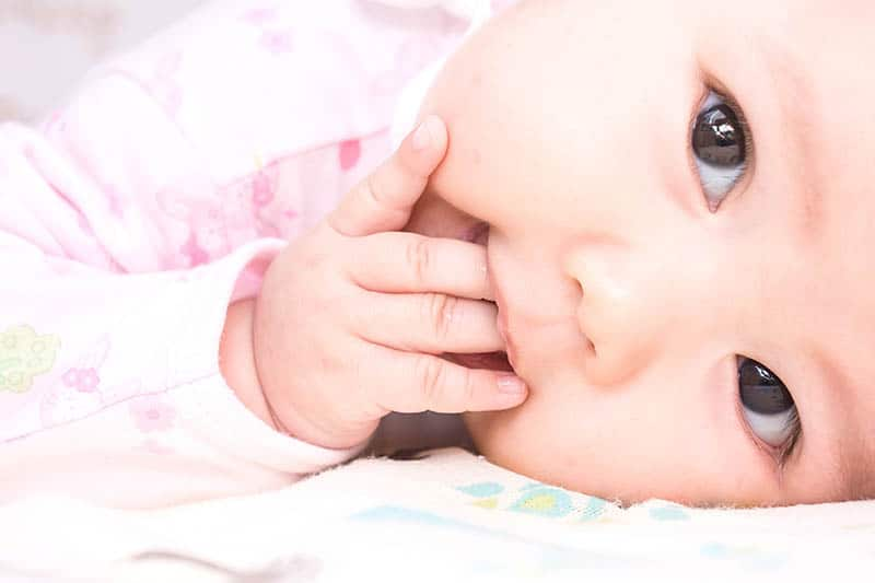 sweet baby girl holding hand in mouth beacuse of teething