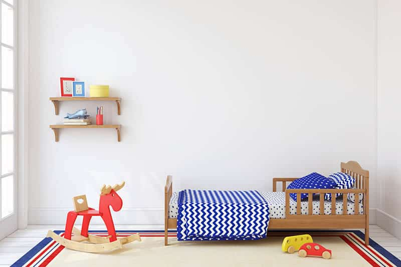 toddler bed with children's items and toys in the room