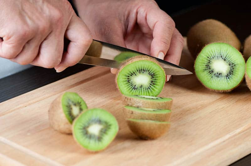 woman cutting kiwi on the wooden cutting board