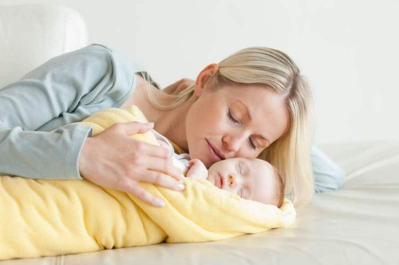 woman gently kissing her sleeping baby wrapped into yellow blanket on the bed