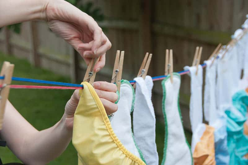 woman hangs cloth diapers on a clothesline to dry in the sun