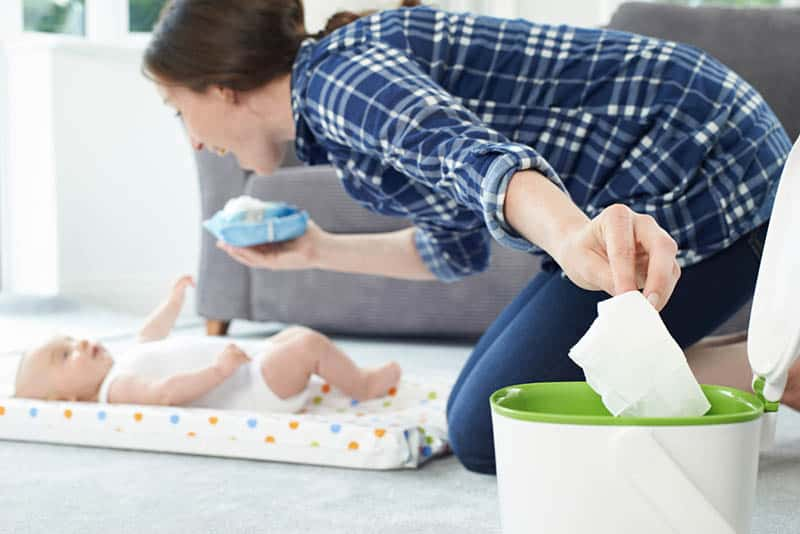 woman smiling to baby and throwing a wipe into the bin in the bedroom