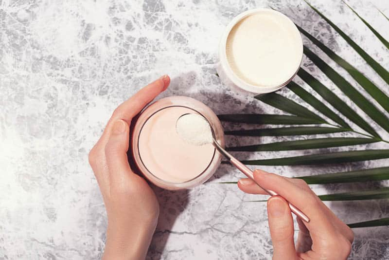 woman taking protein powder with spoon with glass of yogurt and a plant on the table