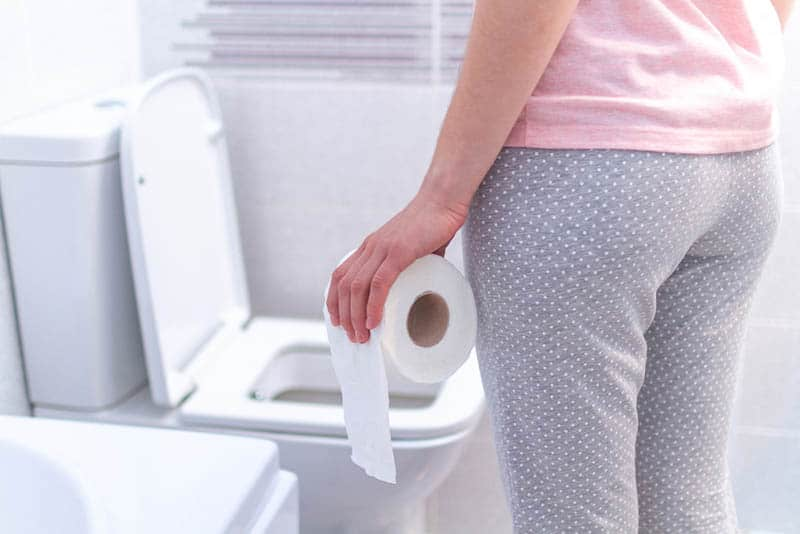 woman wearing a pajama holding a paper roll in the bathroom