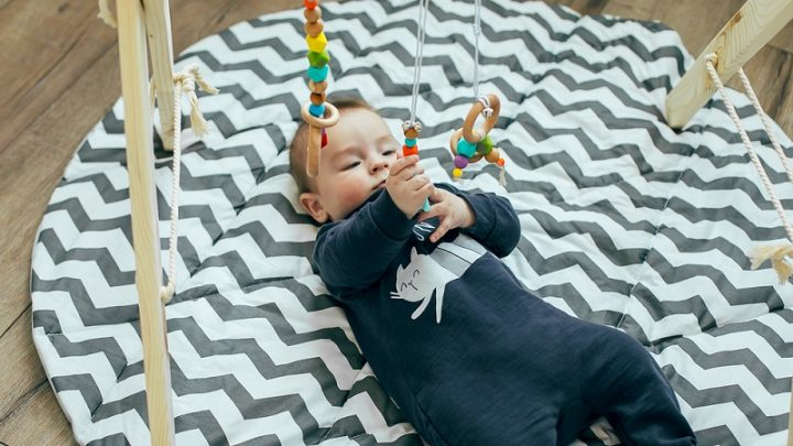 baby playing on the floor with a wooden gym