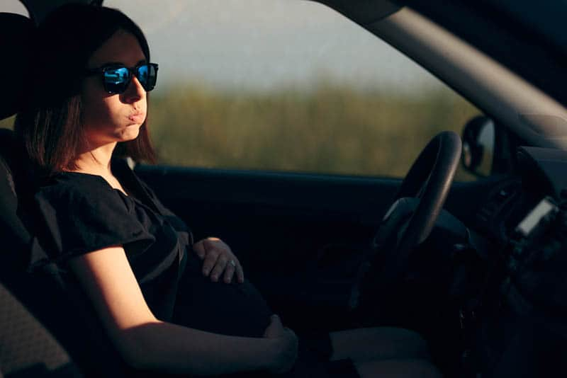 worried pregnant woman holding for belly in the car