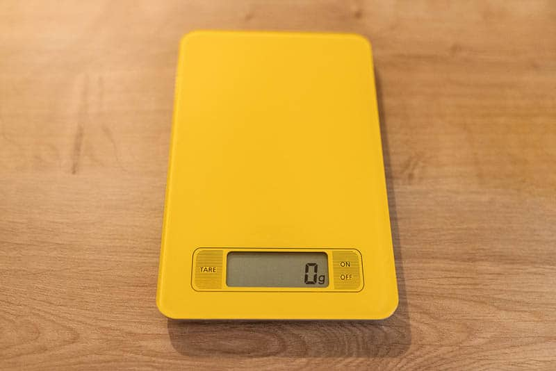 yellow kitchen scale showing 0g at display on the wooden table