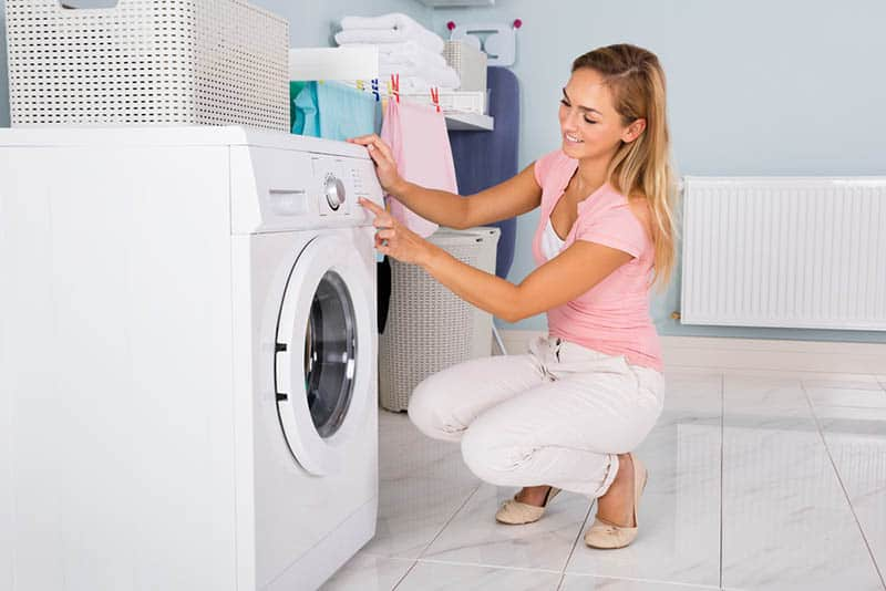 young happy woman using washing machine in the bathroom