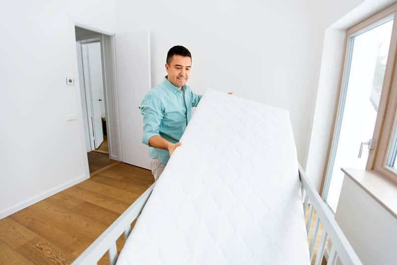 young man putting mattress in baby bed in the room at home