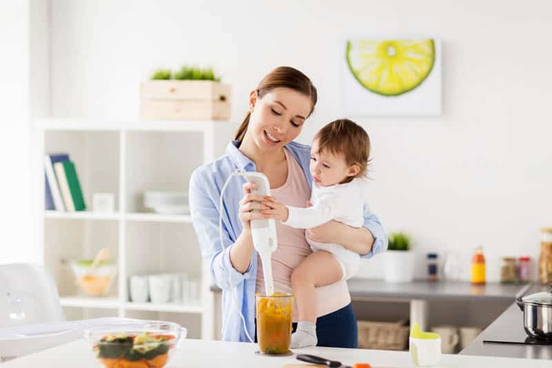 young mother holding baby girl and blending food in the kitchen