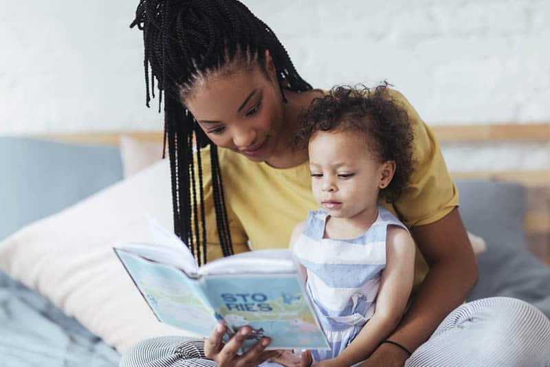 young mother reading a book with her cute little daughter on the bed