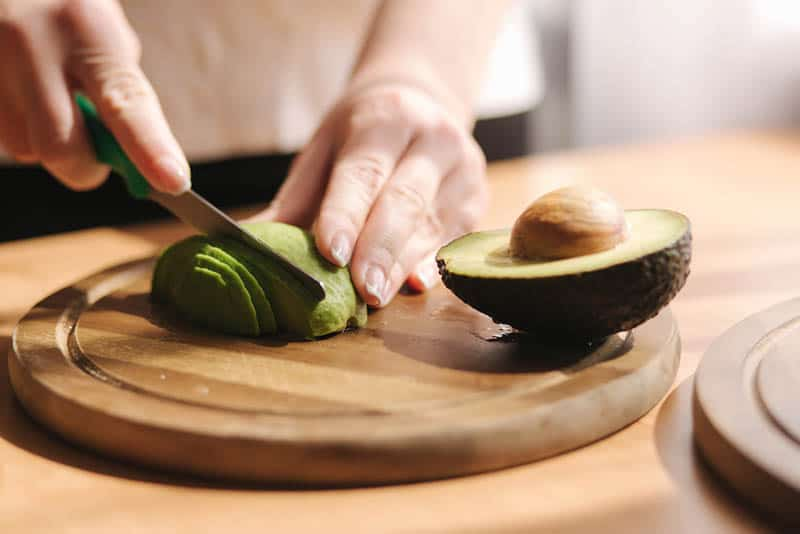 young woman cutting an avocado on the wooden board on the table