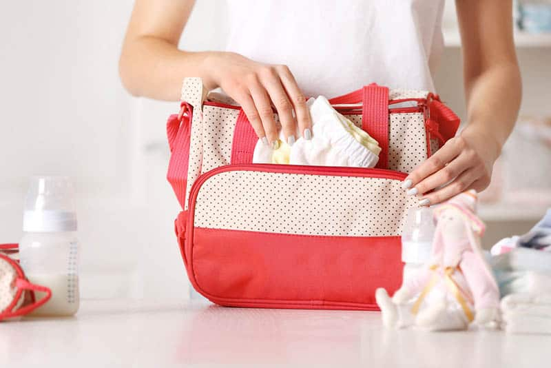 young woman packing a diaper bag with baby items
