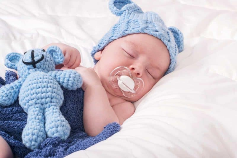baby sleeping with a pacifier in his mouth