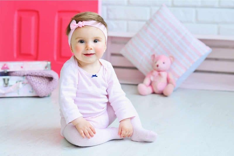 adorable girl wearing pink clothes and trendy headband while posing for a photo
