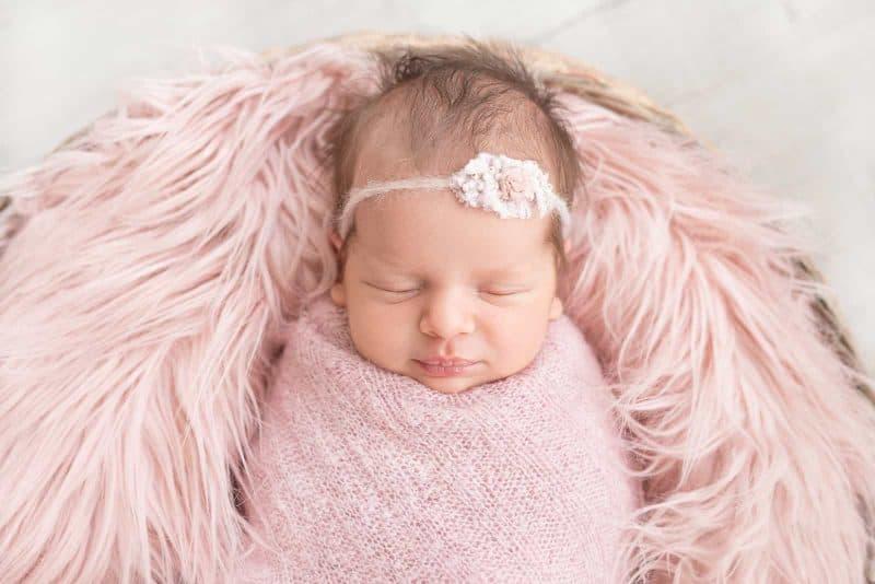 sleeping newborn baby girl in a basket