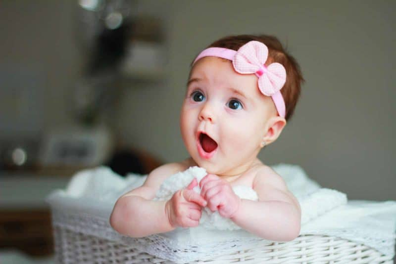 baby girl wearing a bow with a surprised facial expression