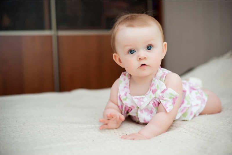 beautiful baby girl with big blue eyes lying on the bed