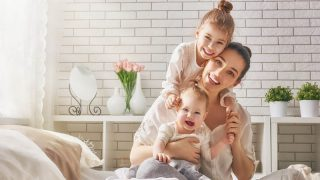 beautiful young mother hugging her daughters on the bed