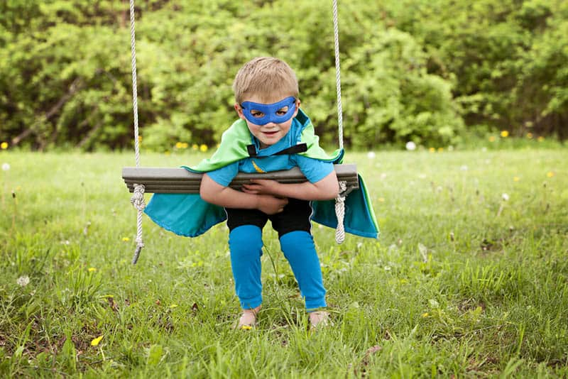 Adorable little boy dressed in a cape and mask playing superhero