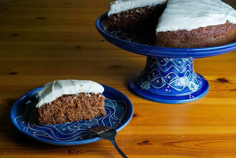 Applesauce cake with cream cheese frosting on the blue stand on the table