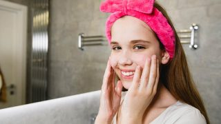 teen girl with pink headband washing her face