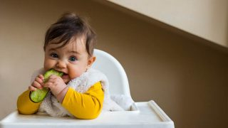 sweet baby in a high chair eating a cucumber