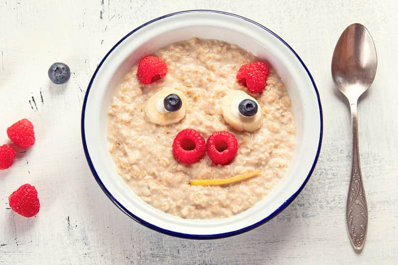 Cute pig face shaped oatmeal with fruits for baby breakfast