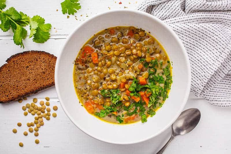 Homemade vegan lentil soup with vegetables and cilantro in plate on the table