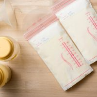 two storage bags of breast milk with pump and bottles on the table