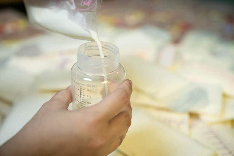 Mother is pouring milk from breast milk storage bags to baby bottle with measuring scale