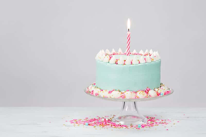 Pastel blue birthday cake with pink sprinkles on the table