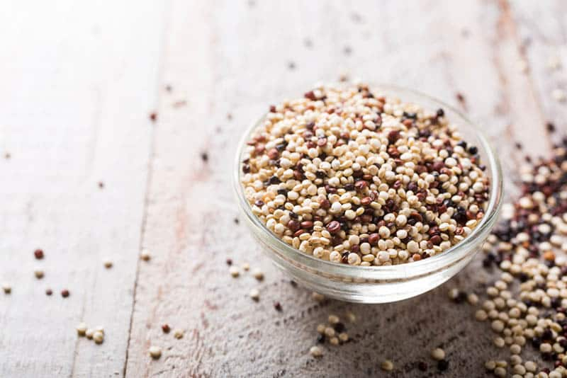 Pile of mixed raw quinoa on the wooden table
